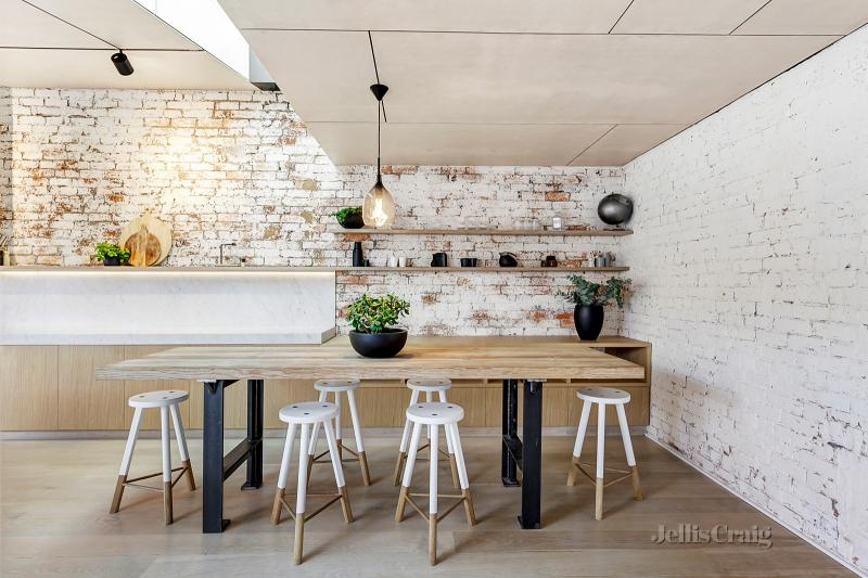 A kitchen with exposed white brick wall
