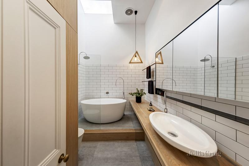A narrow bathroom complete with vanity, shower and freestanding bath