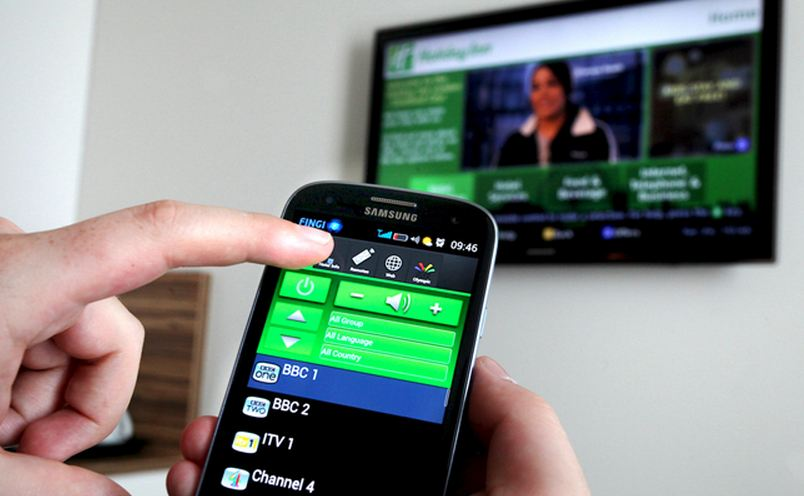 A person controls their TV via a mobile phone