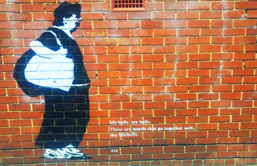 A wall mural on a brick wall of a homeless women dedicated to Michelle.