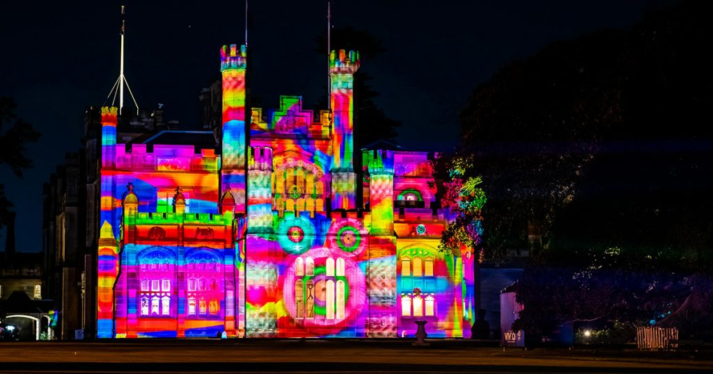 The Vivid Event in Sydney shows a building lit up in colours from multiple projections