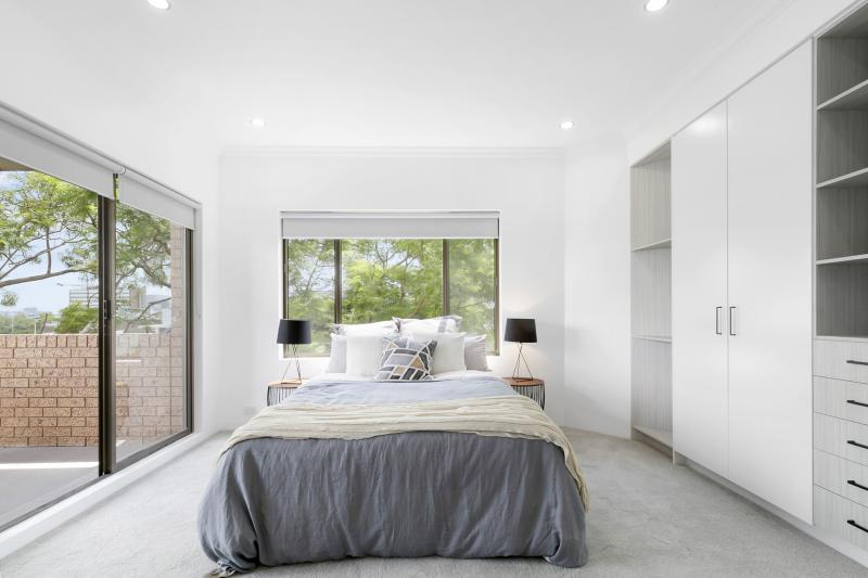 A bedroom with plenty of natural light and grey carpet