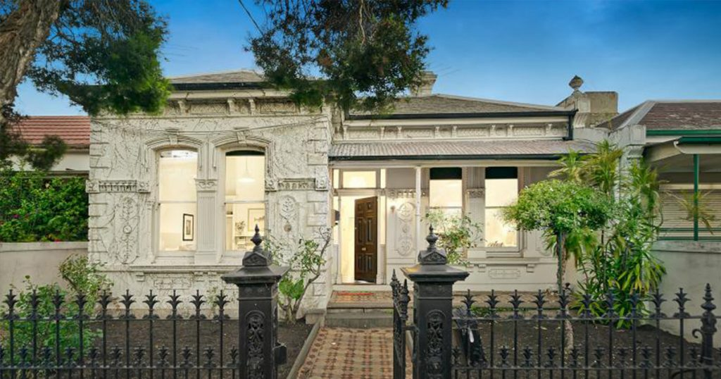 One of the best investment homes for Victoria, a brick home with a black picket fence.