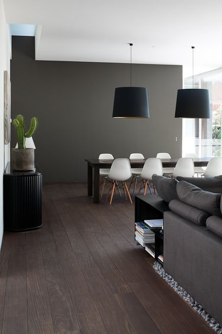 A living room with a dark colour scheme including dark floorboards and a dark grey feature wall.