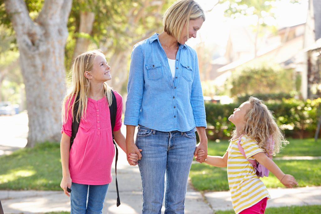Has your suburb value grown? A women walks with her children down the street
