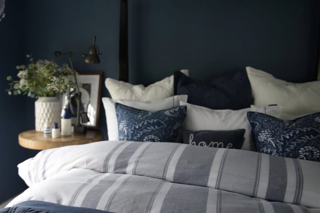 A bedroom with a dark blue feature wall and light bedspread.