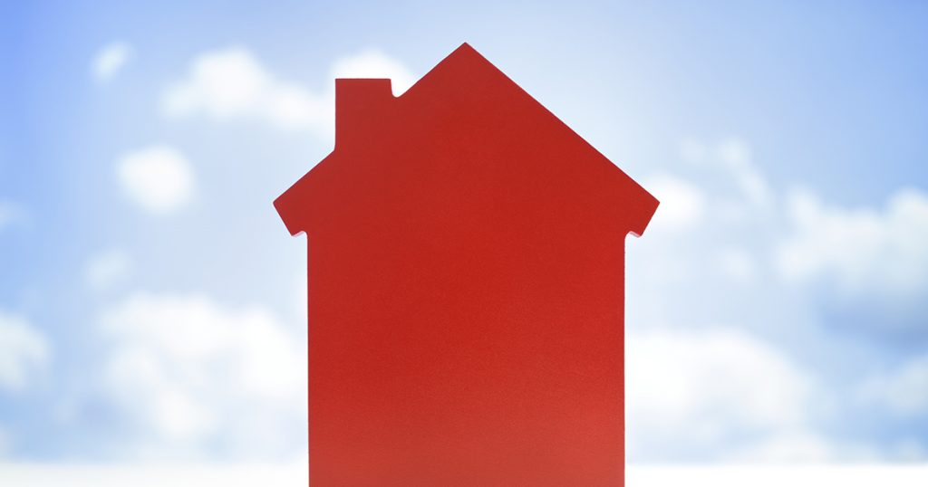 A big red house with the sky in the backgorund
