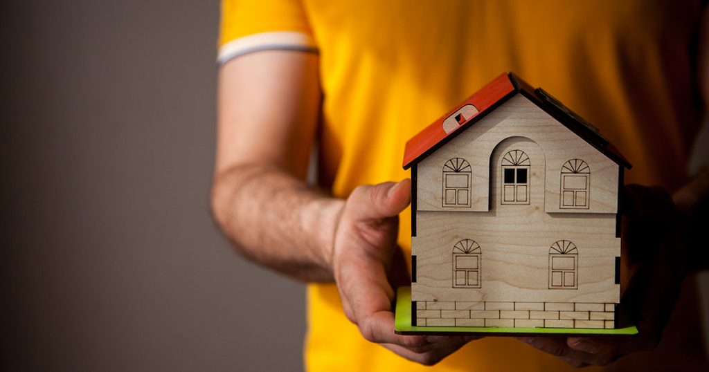 A man in orange shirt holds a model house