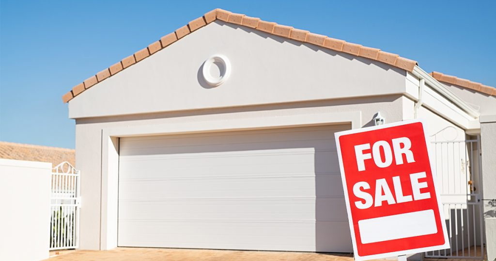 A property with a 'for sale' sign out the front