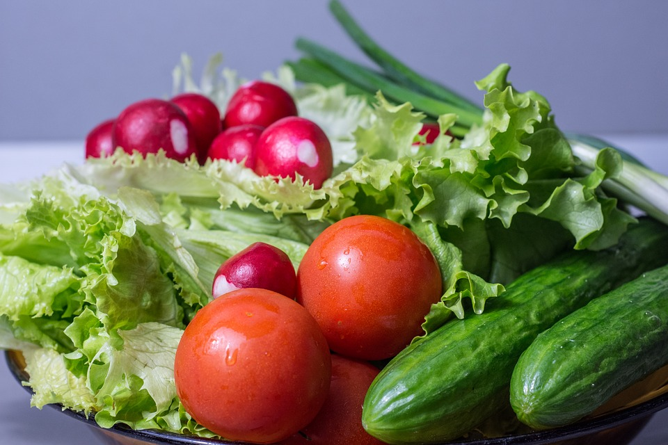 A healthy salad with lettuce, tomato, spring onion, raddishes and cucumber