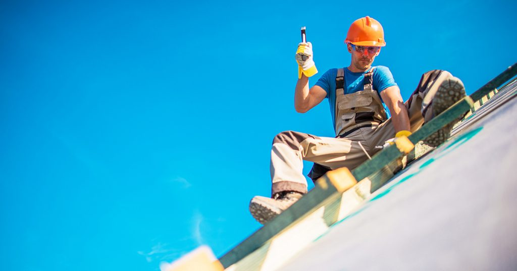 A tradesman works on the roof of a home