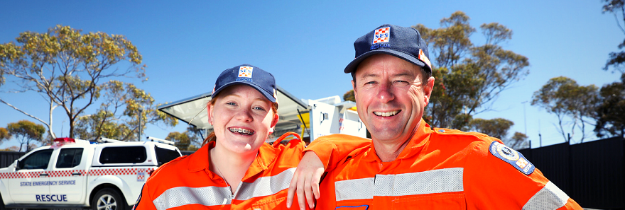 Two SA State Emergency Service volunteers standing in front of a SES vehicle.