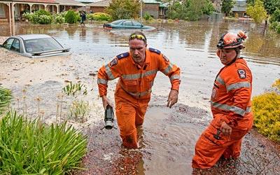 Two operational SES volunteers pumping flood water