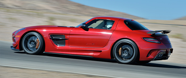 Lewis Hamilton driving his red Mercedes AMG SLS black series