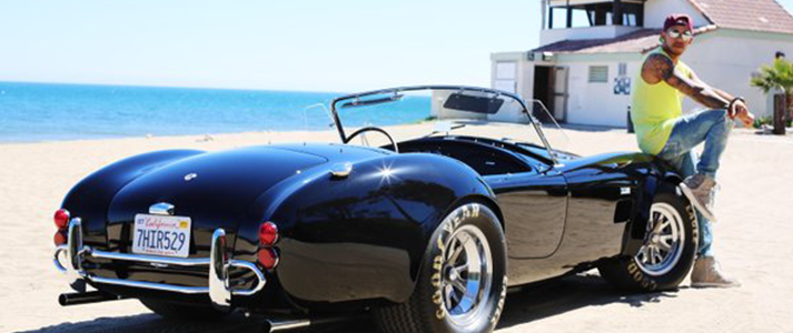 Lewis Hamilton sitting on his black Shelby Cobra 427