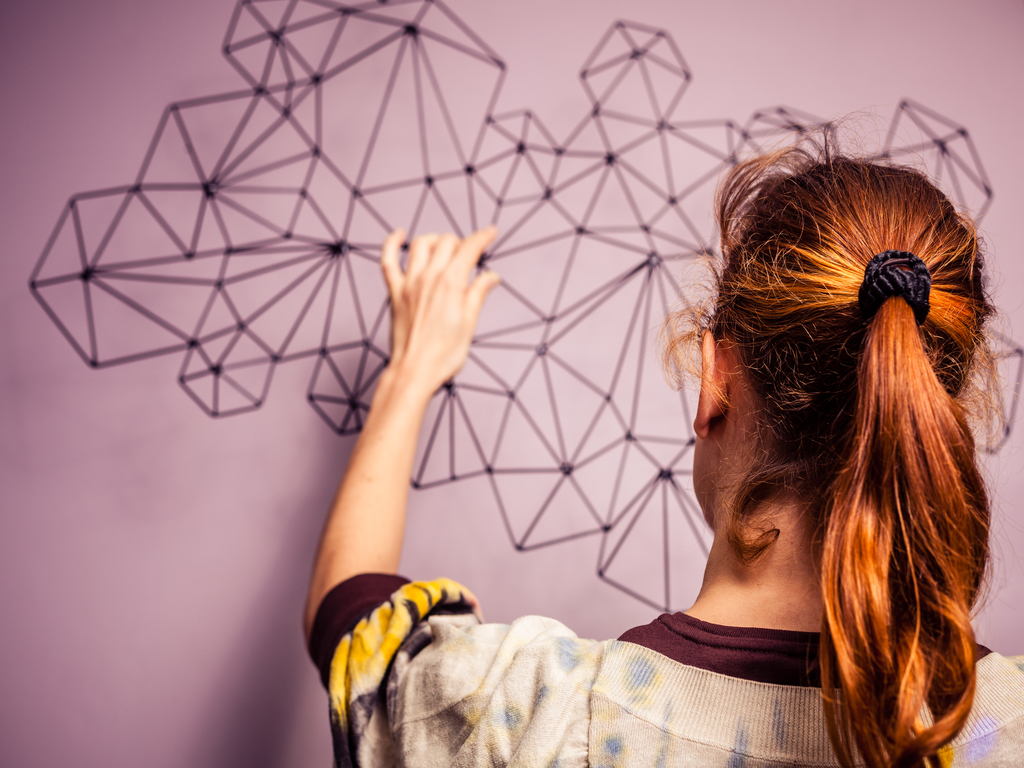 Young woman hanging a piece of geometric art on her wall