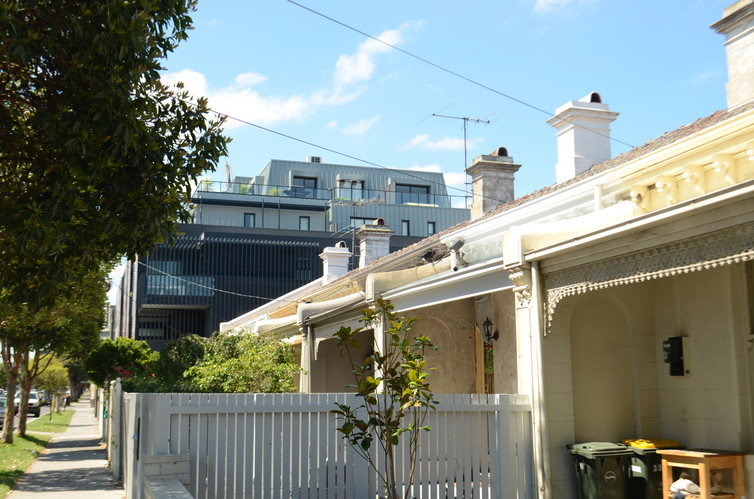 A row of older terrace houses in the same style runs into a large apartment block on Burnley Street. On some streets rows of large apartments now dominate the streetscape. Tod Jones