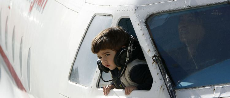 A child leans from  the cockpit window of a plane at a kindergarten in the town of Rustavi