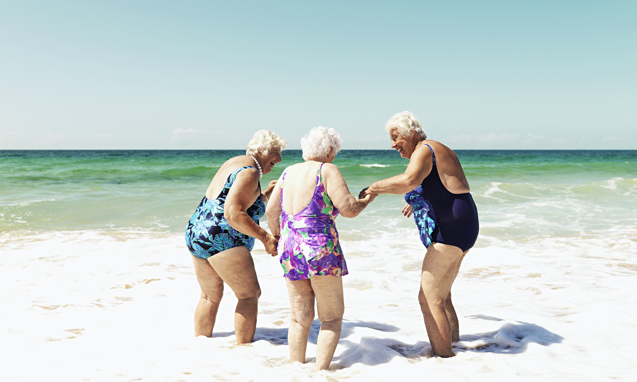 Three old ladies laughing on beach in the surf