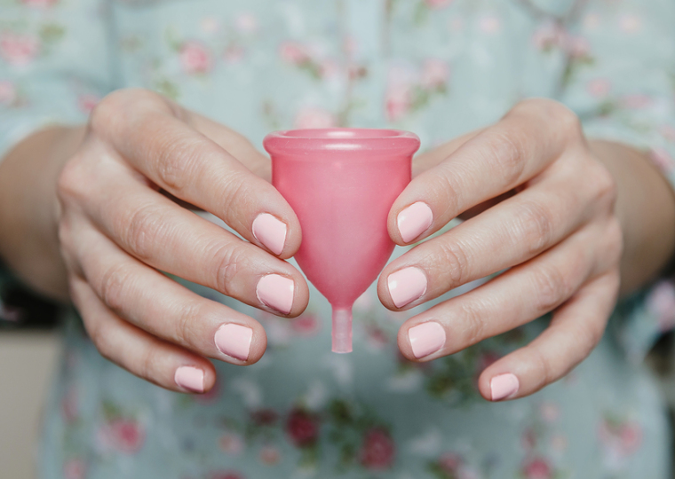 Woman hands holding pink menstrual cup. Modern female intimate hygiene concept.