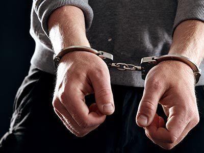 man's hands in hand cuffs