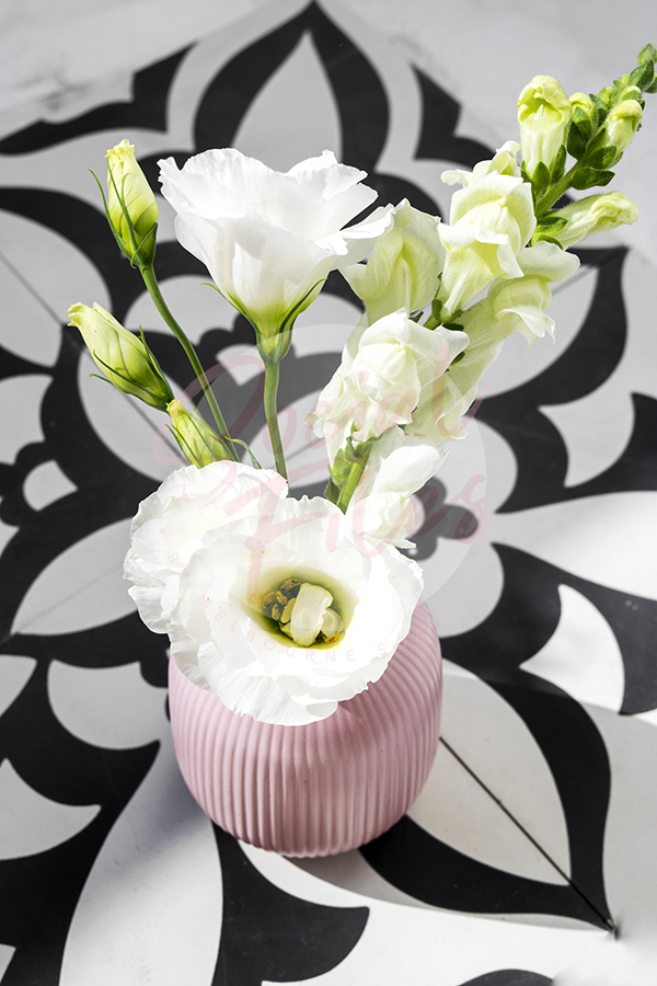 White Flowers In Pink Vase Sitting On Black And White Tiles