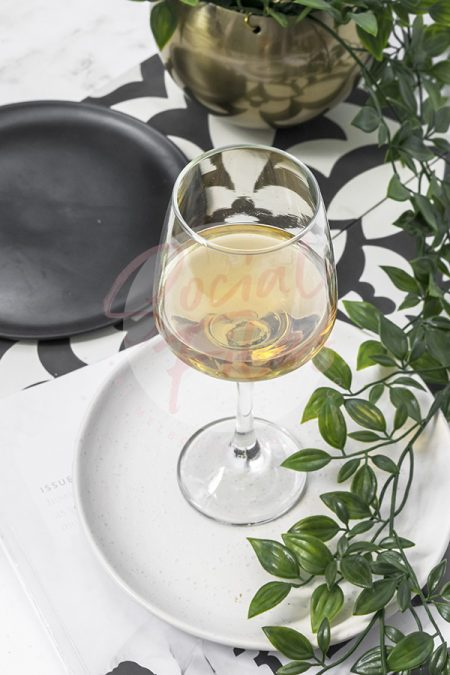 Wine glass filled with a beverage, sitting on a white plate with black and white tiles in the background