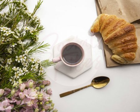 Coffee in pink espresso cup, with pretty florals and croissant - watermarked image