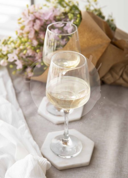 Wine glasses filled with a beverage, sitting on fabric with pretty florals in background- watermarked image
