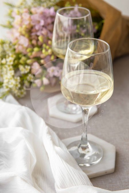Wine glasses filled with a beverage, sitting on fabric with coasters, pretty florals in background - watermarked image