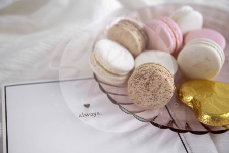 Valentine's Day flatlay with Always greeting card with pink and white macaroons on plate and white fabric - watermarked.