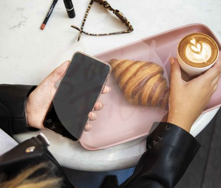 Girl holding coffee and iPhone with croissant on pink plate with sunglasses (watermarked)