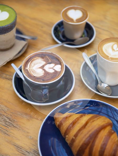 Coffee varieties on wooden table with croissant (watermarked)