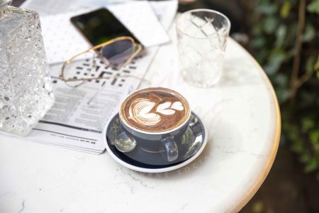 Coffee on marble table with iPhone, newspaper and glasses (watermarked)