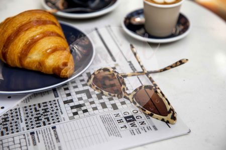 Coffee on marble table with croissant, crossword and sunglasses 02 (watermarked)