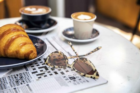 Coffee on marble table with croissant, crossword and sunglasses 01 (watermarked)