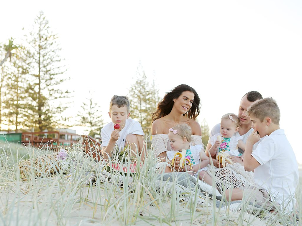 Sophie Guidolin and family sitting at the beach wearing white outfits