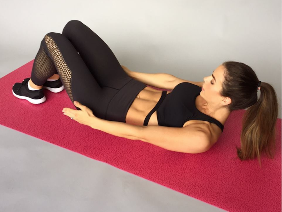 Sophie Guidolin lying on a yoga mat doing ab toe touches