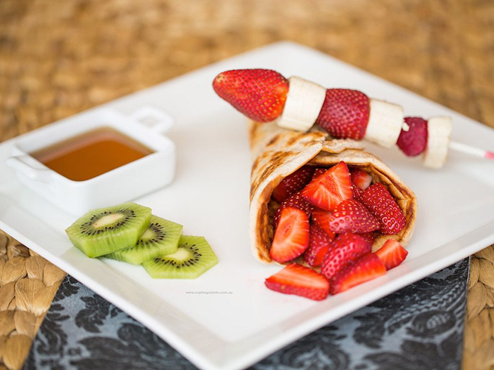 Quinoa pancakes with strawberry and kiwi on a white square plate