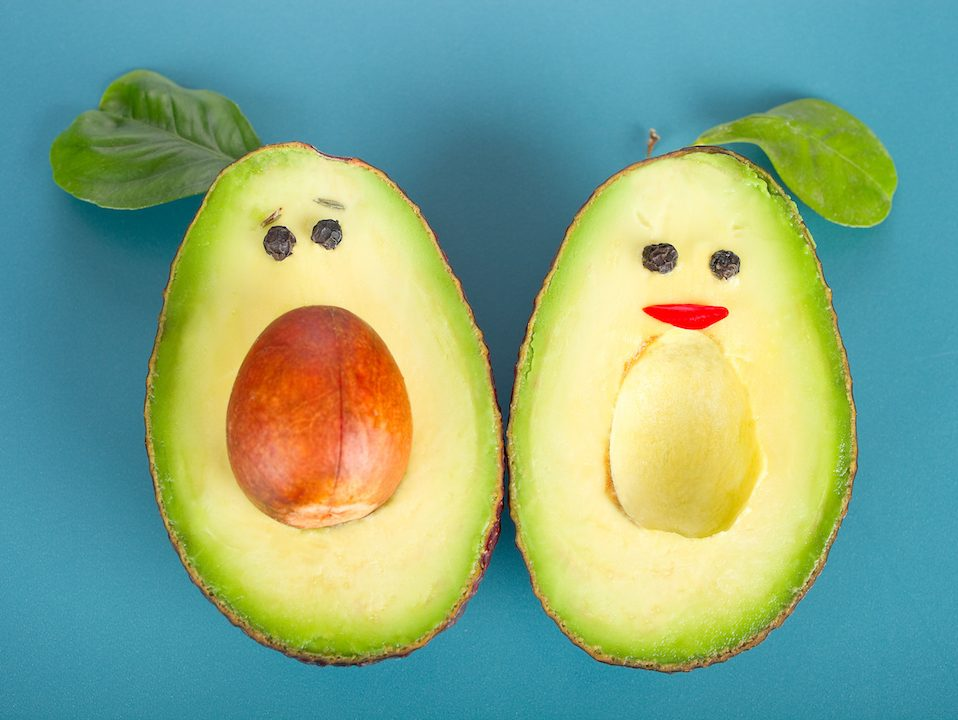 Avocados with smiling faces top view