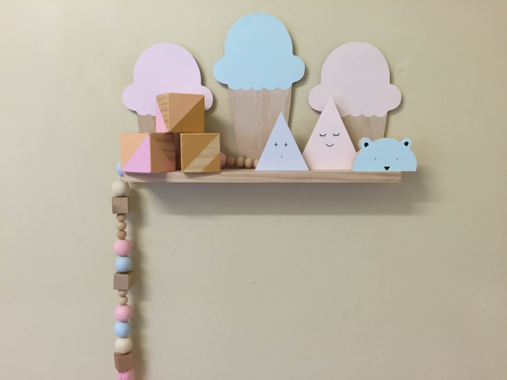Pastel pink and pastel blue ice cream cone shelf inside a baby nursery