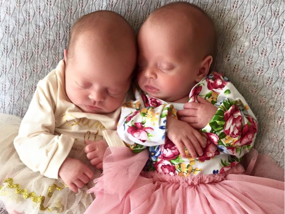 Newborn identical twin girls in adorable tutus with their heads touching