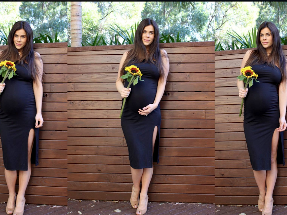 Sophie Guidolin twin pregnancy photo wearing a black dress and holding a sunflower