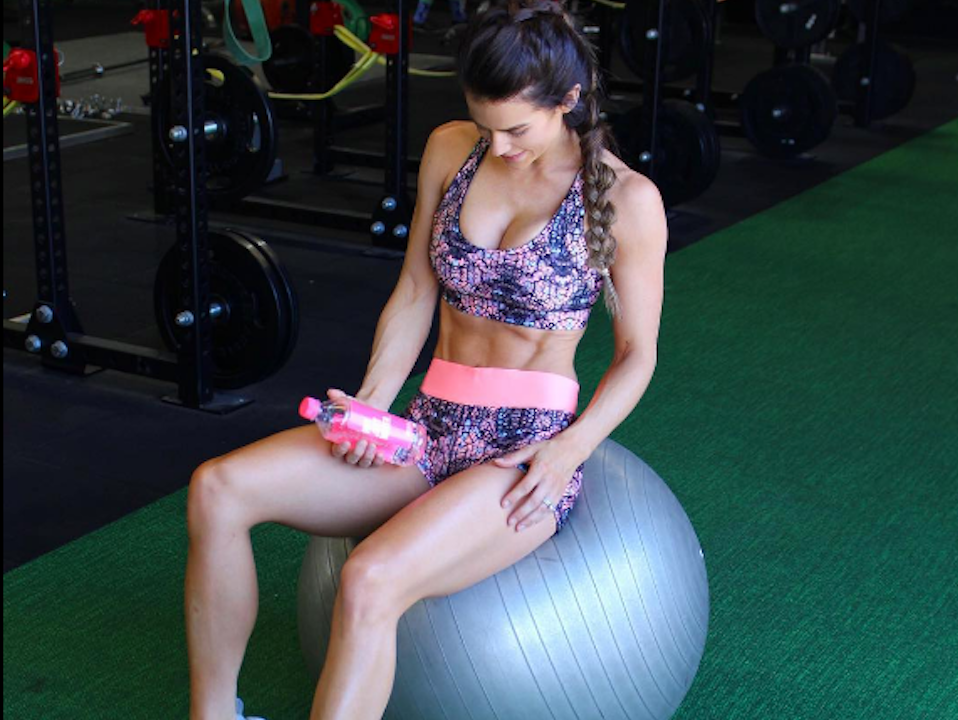 Sophie Guidolin in bright activewear on a gym ball looking down