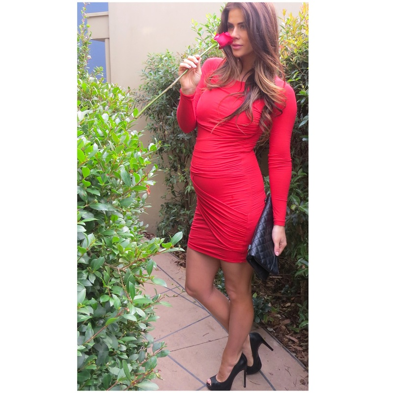 Sophie Guidolin wearing a red dress while pregnant sniffing a rose
