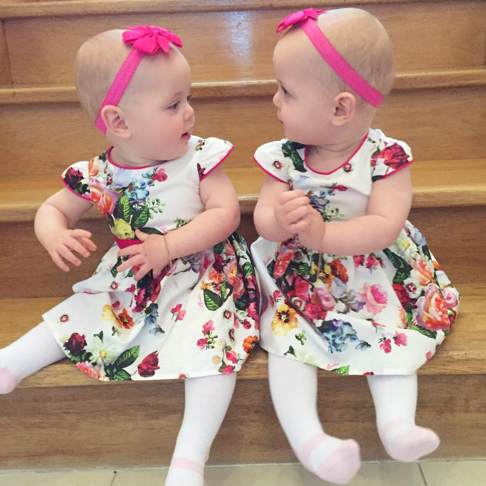 Identical twin girls in pink headbands and cute socks sitting on steps