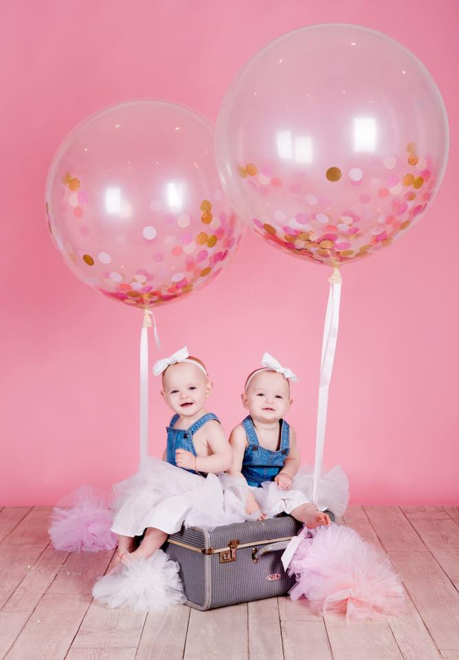 Identical twin baby girls against a pink backdrop with big balloons for photoshoot