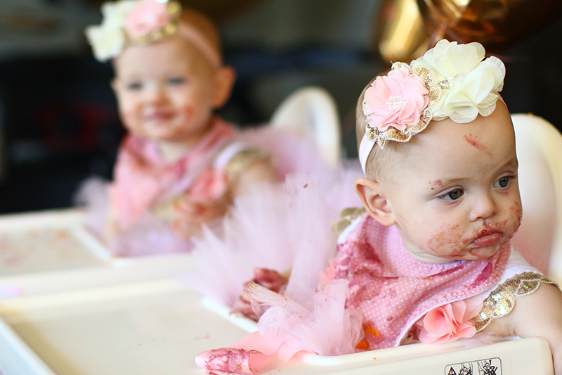 Cute baby girls with food on their face sitting in high chairs