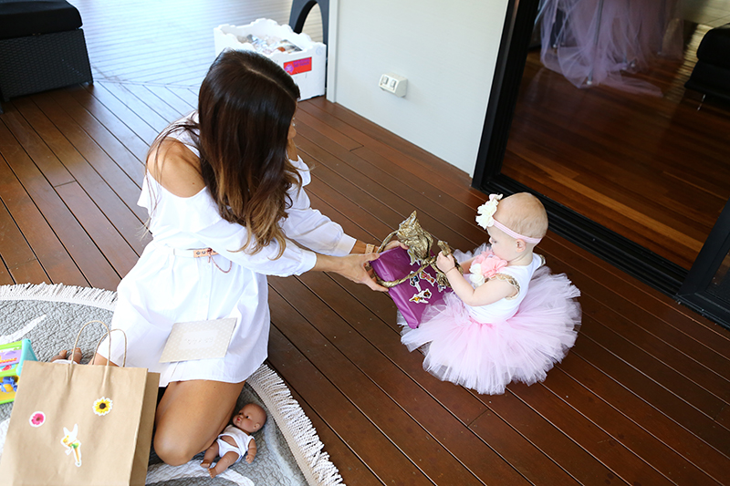Sophie Guidolin with baby opening presents at birthday party