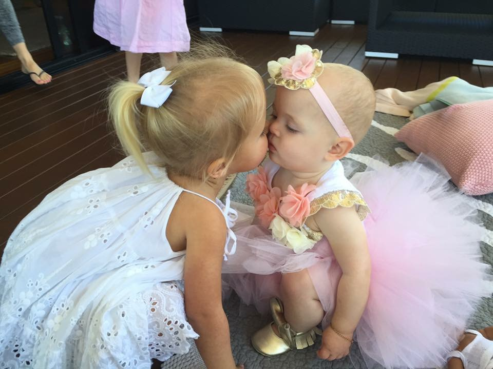 Baby girls sharing a cute kiss at a birthday party